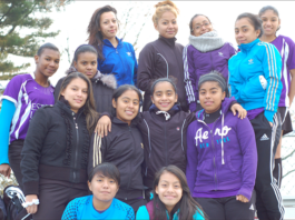 A group of young girls on a soccer team posing for a photo