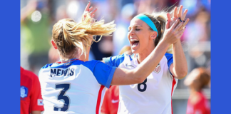 Women's soccer players high five on the field