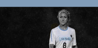"""A womn in soccer uniform with the number """"8"""" on her jersey walking on field with a black background"""