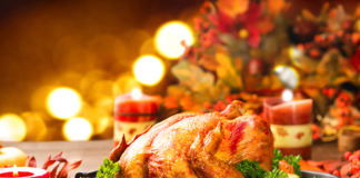 A Thanksgiving turkey on a serving plate surroundedby garnish with lights in the background