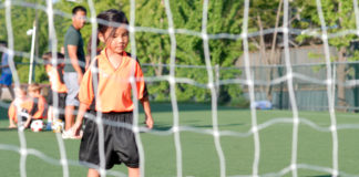 A small girl kicks soccer ball toward net; Image is from behind the net with girl in background