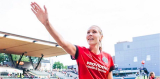 Up close shot of a tall female soccer player waving to fans as she walks on field
