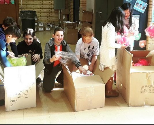Boys and girls opening boxes of new sports equipment