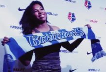 A woman holding a scarf with a professional women's soccer teams logo at the NWSL draft