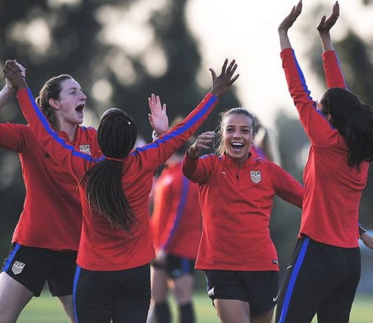 A group of young female players jumping and waving arms in the air