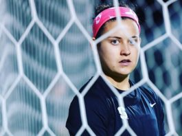 A female soccer player stands behind the goalie net