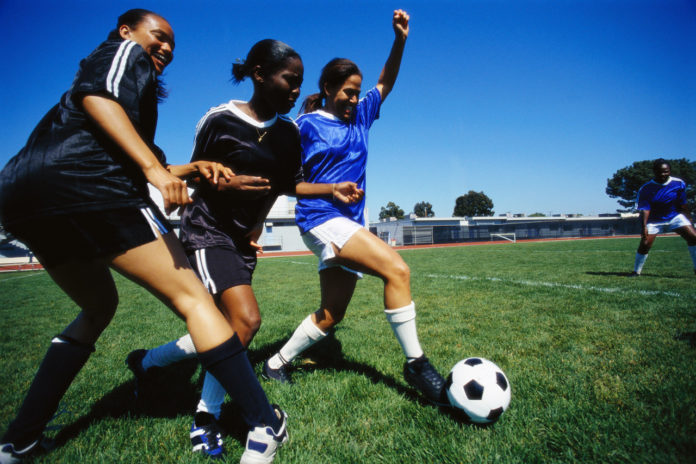 Female Soccer Players Kicking Ball